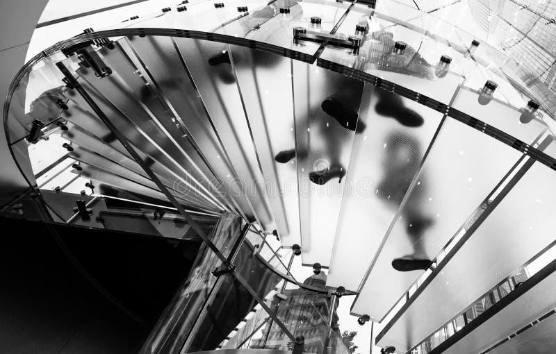 走的人民现代玻璃楼梯剪影  免版税图库摄影