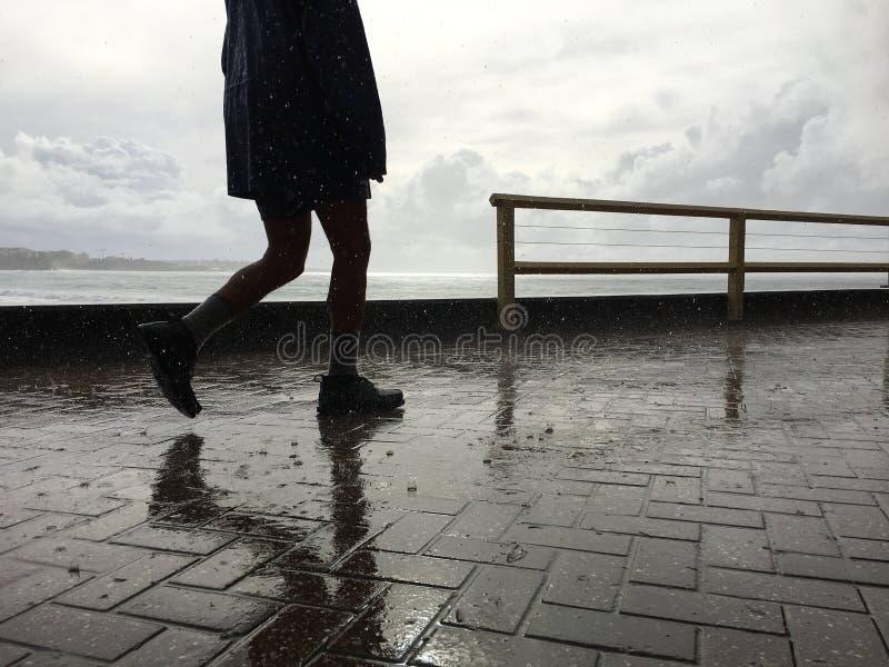 走的人,落在路面的雨 库存图片