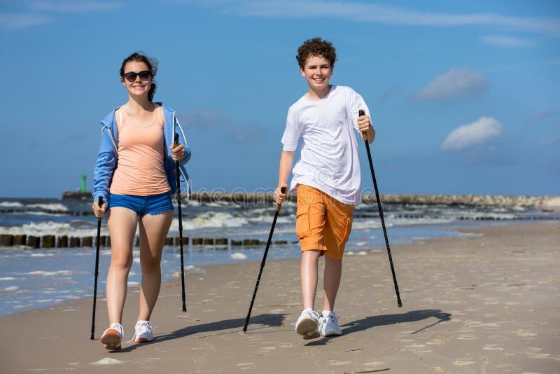走的北欧人-解决在海滩的青年人 库存图片