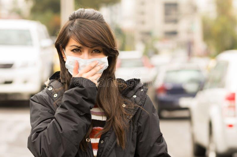 走的女孩戴着一个面具在城市 免版税库存图片