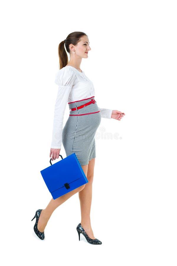走的怀孕的女实业家画象有文件案件的 免版税库存照片