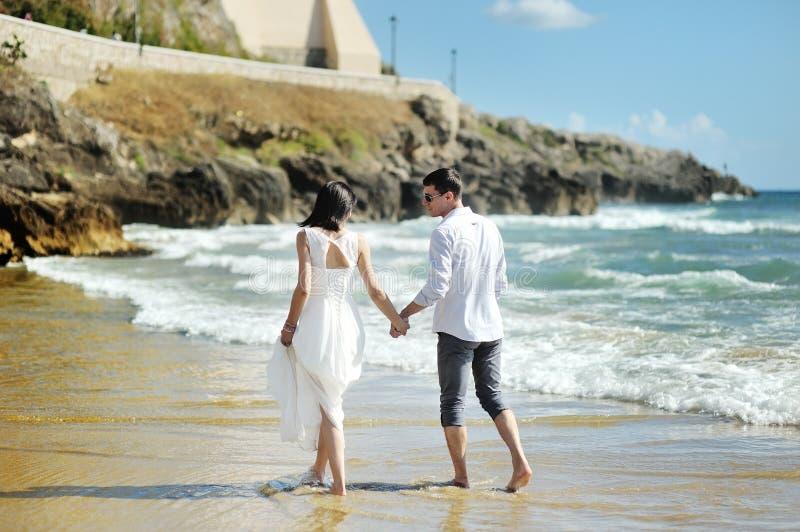 走的新娘和新郎结合在一起使手临近海,斯佩尔隆加 免版税库存图片