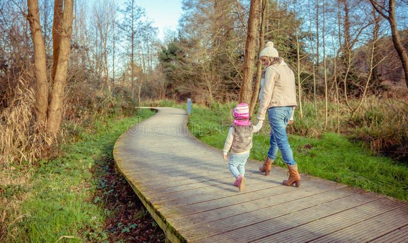 走的母亲和的女儿结合在一起使手 免版税图库摄影