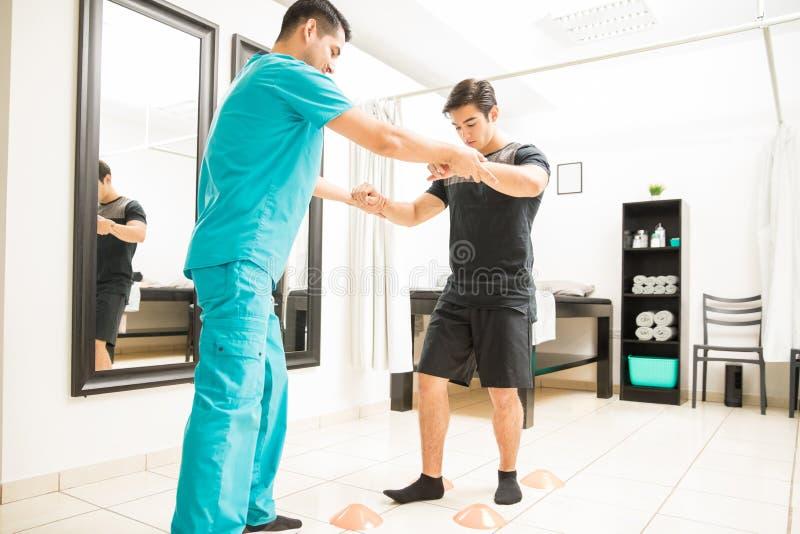 走的生理治疗师帮助的运动员在锥体之间在Hospita 库存照片