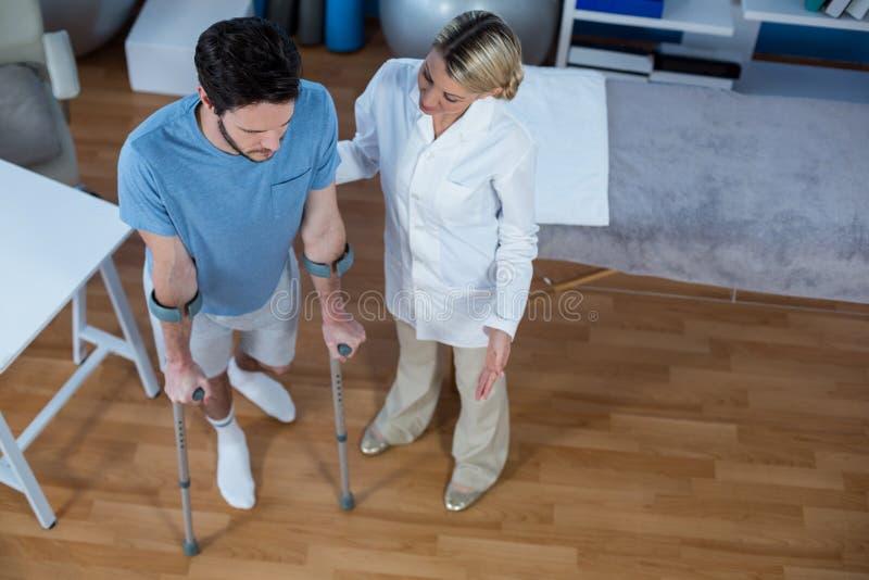 走的生理治疗师帮助的患者与拐杖 库存照片