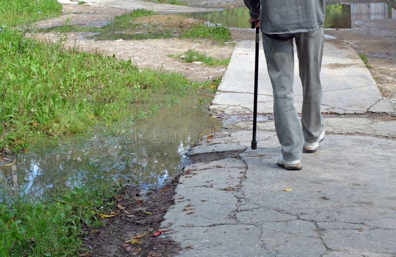 走的老人用棍子 免版税库存照片