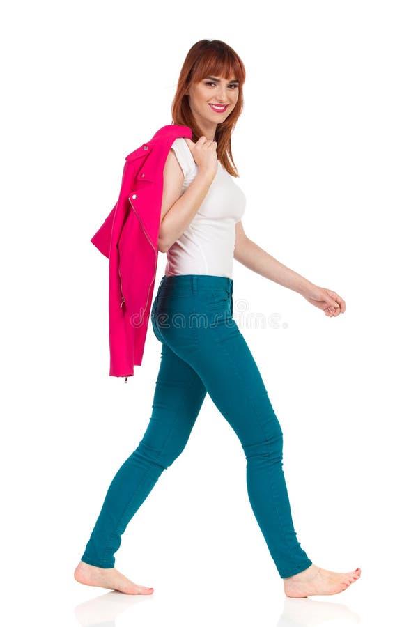 走的赤足愉快的年轻女人拿着在肩膀的夹克 库存图片