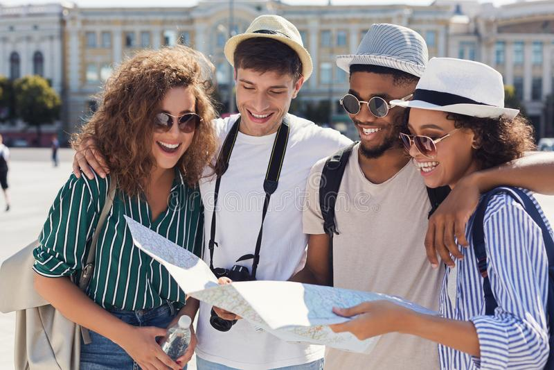 走穿过有地图的城市的小组朋友 免版税图库摄影