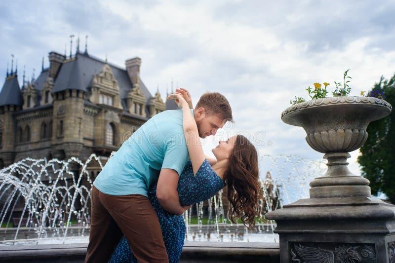 走近城堡的一对年轻爱恋的夫妇 到蜜月的婚礼旅行 库存照片