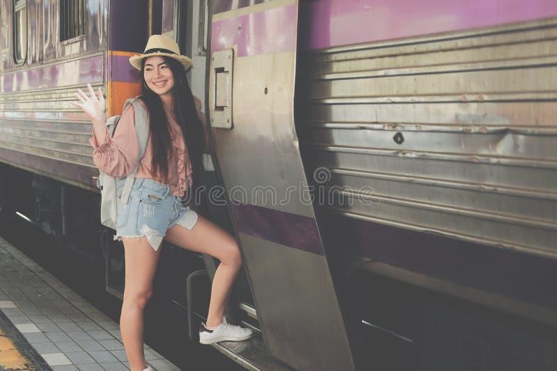 走近妇女旅游的旅客训练在铁路在火车站 旅行旅途旅行概念 免版税库存照片