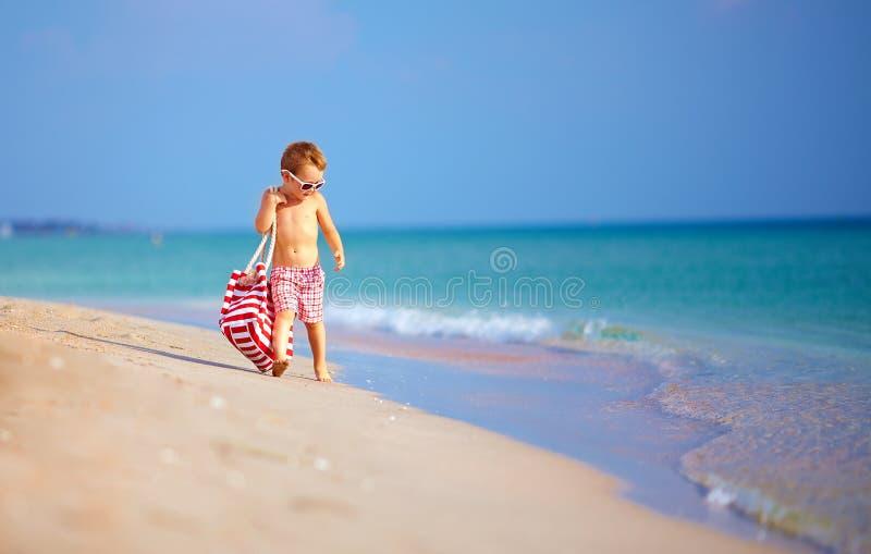 走逗人喜爱的小孩的男孩海边,暑假