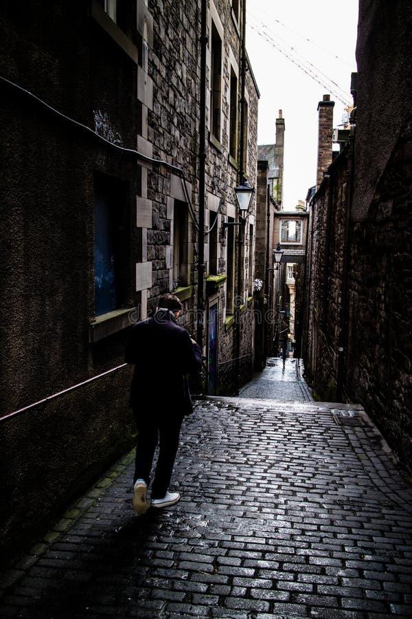 走通过一条稀薄的巷道的一个孤立人在爱丁堡 免版税库存图片