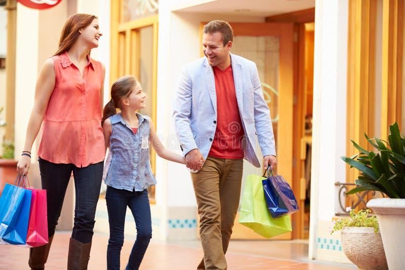 走通过与购物袋的购物中心的家庭 免版税库存图片