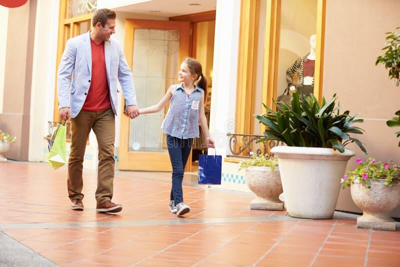 走通过与购物袋的购物中心的父亲和女儿 库存图片