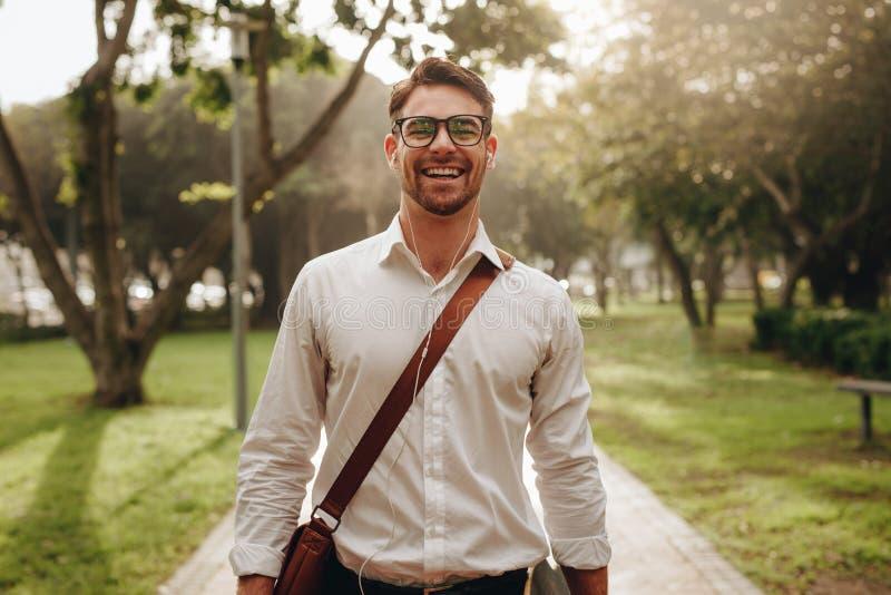 走通过公园的快乐的商人去办公室 免版税图库摄影