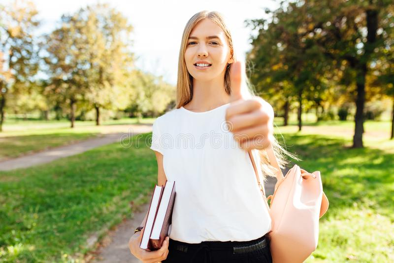 走通过公园的美丽的男女共学女孩拿着书他 免版税库存图片