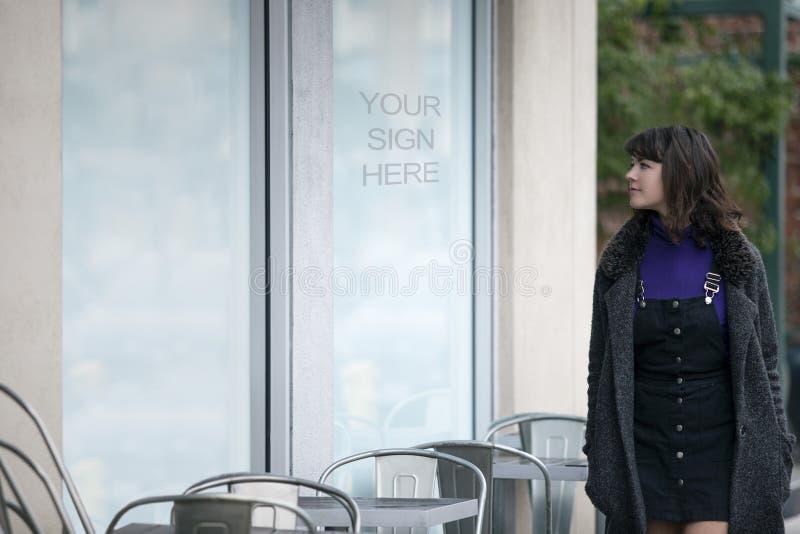 走通过商店窗口标志的妇女 库存照片