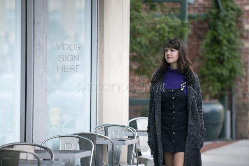 走通过商店窗口标志的妇女 库存图片