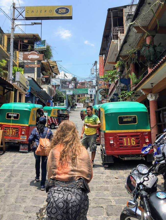 走通过圣佩德罗La拉古纳,危地马拉玛雅村庄街道的一个年轻女性游人  免版税库存照片
