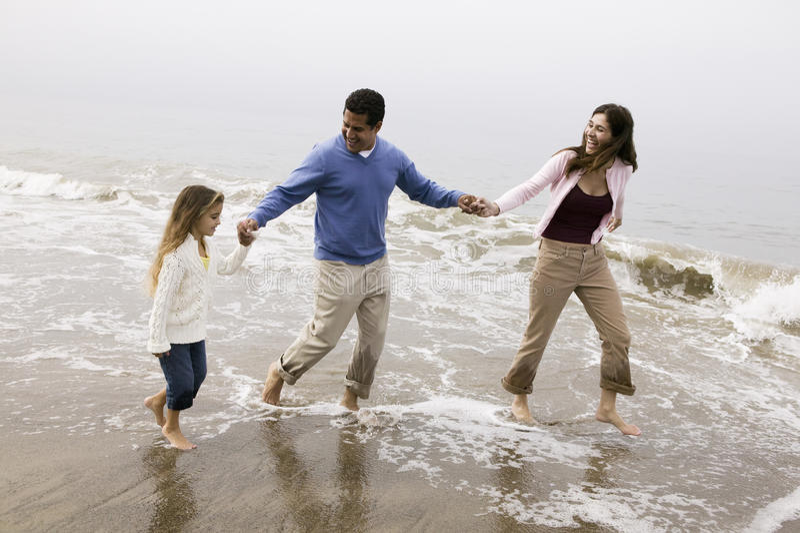 走通过在海滩的海浪的家庭 免版税库存照片