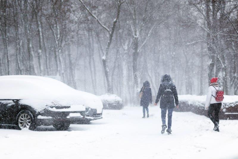 走通过城市街道的人们盖用雪在大雪期间 飞雪在镇在冬天 自然灾害,雪 库存图片