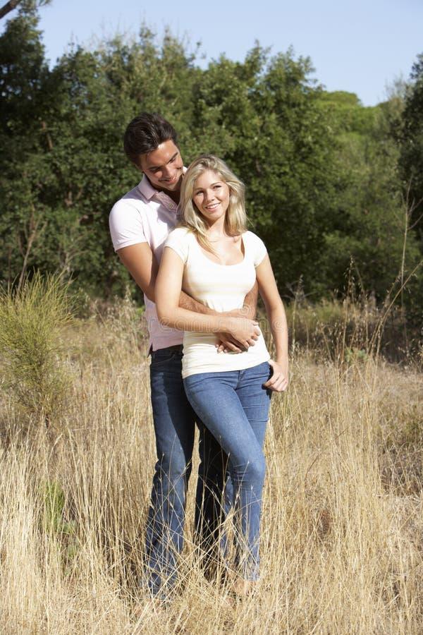 走通过夏天乡下的年轻夫妇 免版税图库摄影