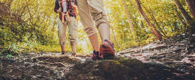 走通过岩石土地的夫人徒步旅行者 在脚的焦点 远足在行动的鞋子对山沙漠足迹道路 图库摄影
