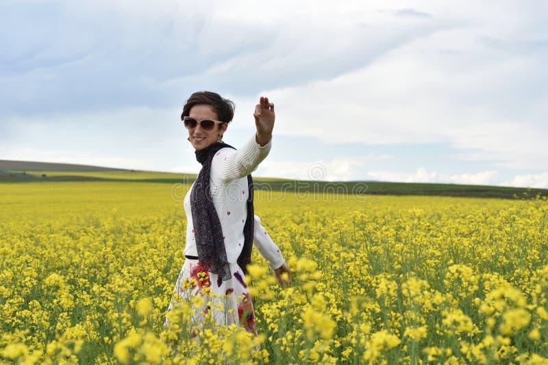 走通过油菜领域的行家女孩 库存图片