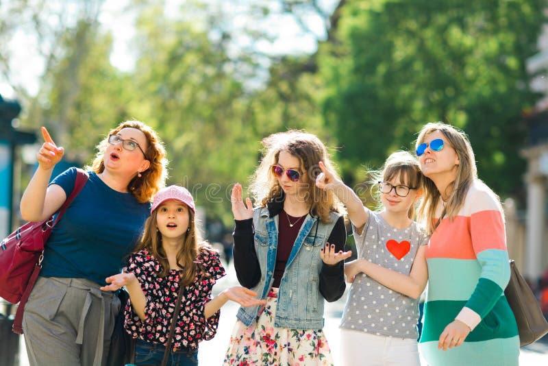 走通过街市的小组女孩-惊奇地指向有趣的地方 免版税库存照片