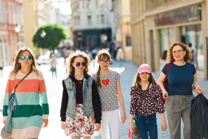 走通过街市的小组女孩-购物的旅行 免版税库存图片