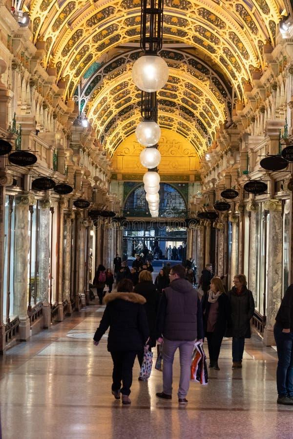 走通过购物的拱廊的顾客 免版税库存照片