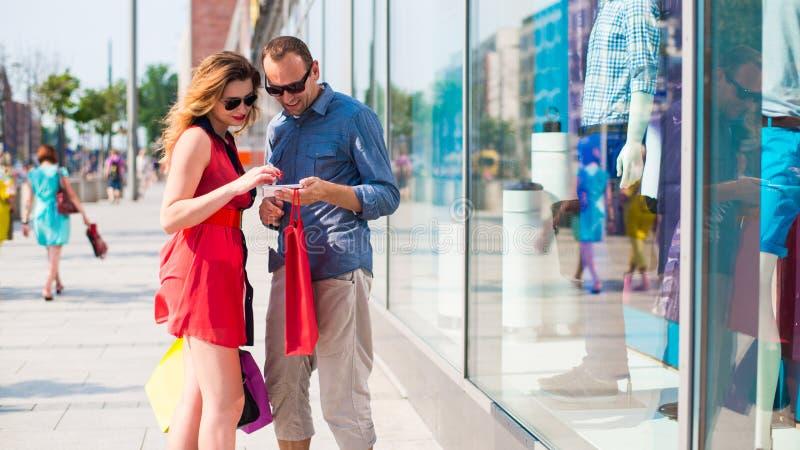走通过购物中心的美好的夫妇运载很多购物袋。 库存照片