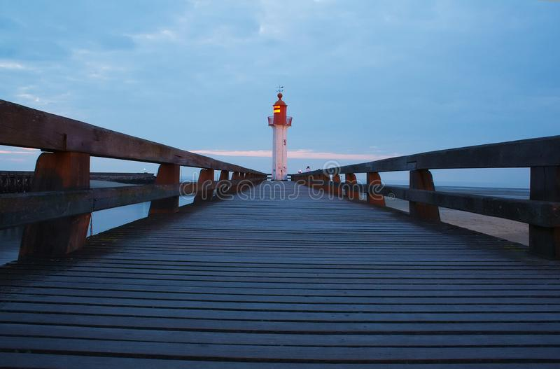 走道和灯塔在日落 免版税库存图片