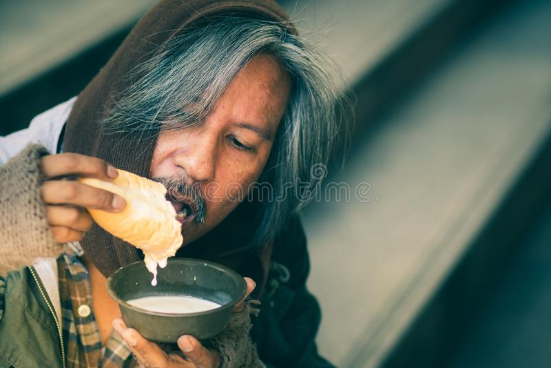 走道街道的台阶的无家可归的人在城市吃面包和牛奶形式仁慈人的给他 免版税库存照片
