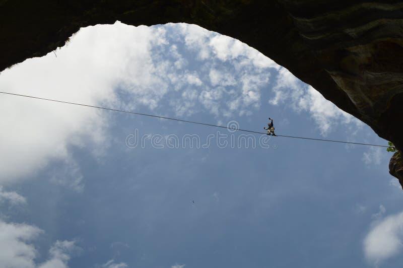走高在天空的一条绳索的年轻highliner 免版税库存照片