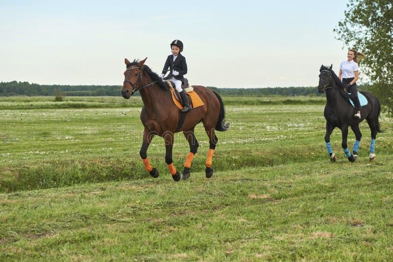 赶走马的小女孩骑师和她的教练 免版税库存照片