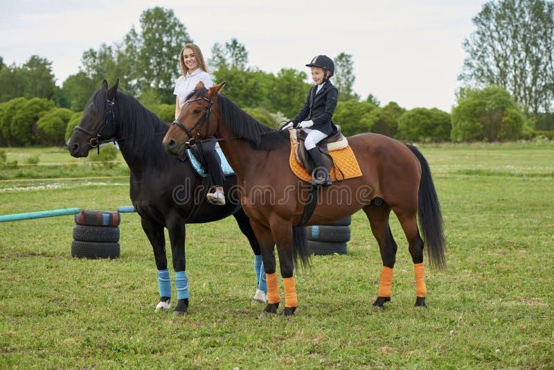 赶走马的小女孩骑师和她的教练 库存图片