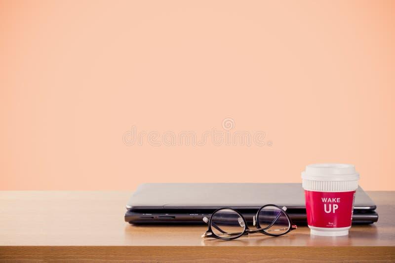 起动与一起使用拿走杯子热的咖啡和膝上型计算机在木桌和橙色背景,葡萄酒口气上 库存照片