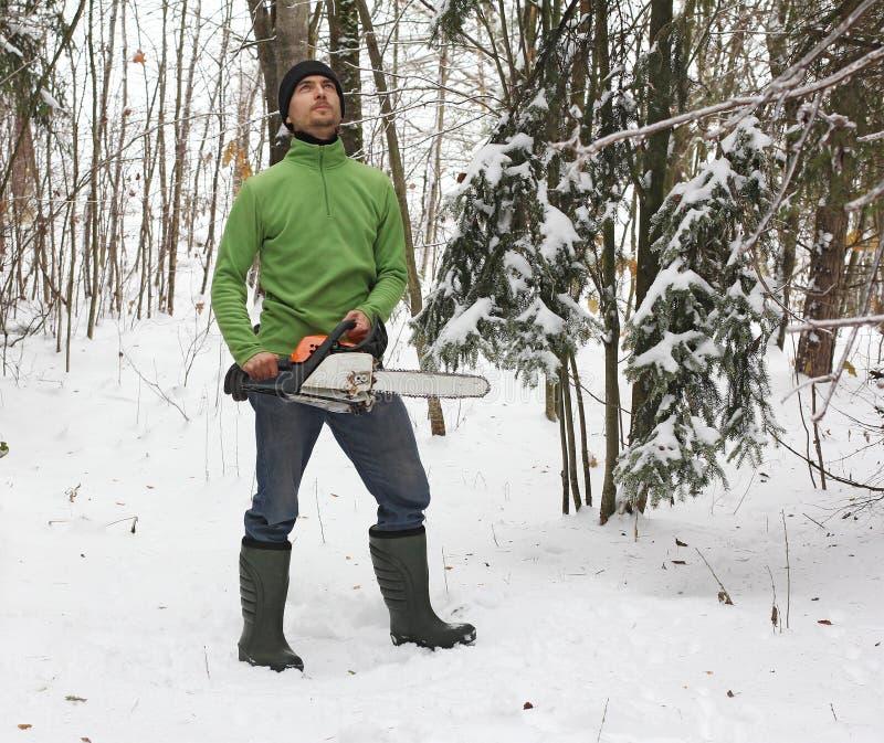 起动的人和一个锯在森林里 库存照片