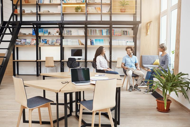 起动,事务,配合概念 小组会议的透视青年人在谈论大现代的图书馆里 免版税库存照片