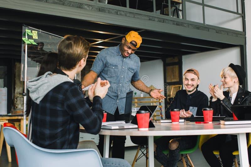 起始的事务,群策群力在见面在办公室内部和使用的年轻创造性的人小组膝上型计算机和片剂 免版税库存照片
