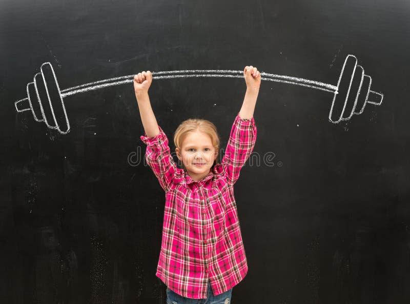 起来drawm杠铃的可爱的小女孩用两只手 库存图片