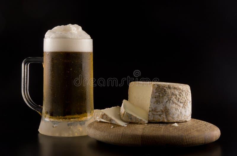 起泡沫的啤酒和乳酪 免版税库存照片