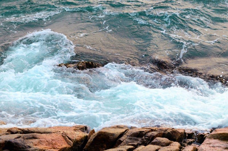 起泡沫的海水击中石海滩、波浪和海滩,自然背景概念 库存照片