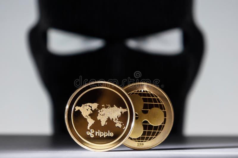 起波纹与强盗黑客佩带的面罩的金黄硬币 免版税库存照片