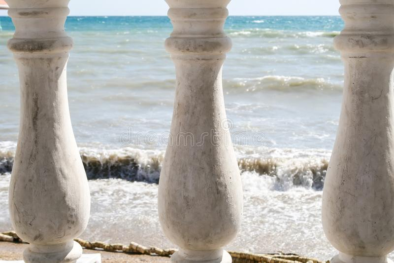 起波纹的海的看法通过篱芭的三根老柱子 免版税图库摄影
