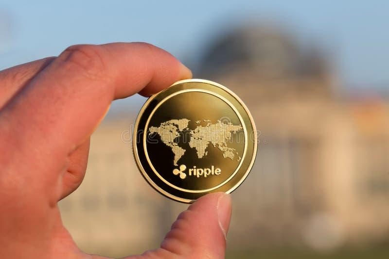 起波纹硬币在德语联邦议会柏林前面的一只手上 免版税图库摄影