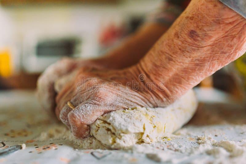起皱纹的老妇人的手细节准备面团的 库存图片