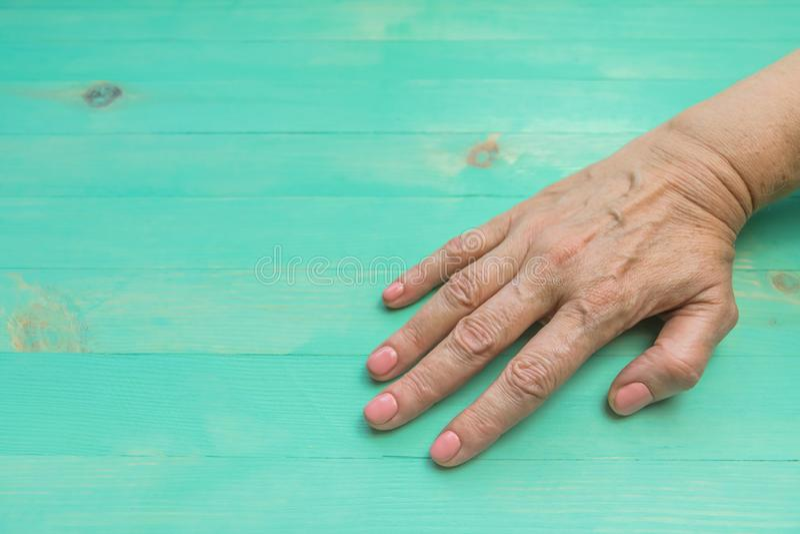起皱纹的资深妇女手皮肤,健康和化妆品概念,拷贝空间的木背景 免版税库存图片