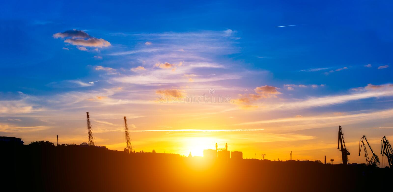 起重机剪影在海口和城市的概述 ?? 明亮的五颜六色的天空和黑剪影 ?? 免版税库存图片